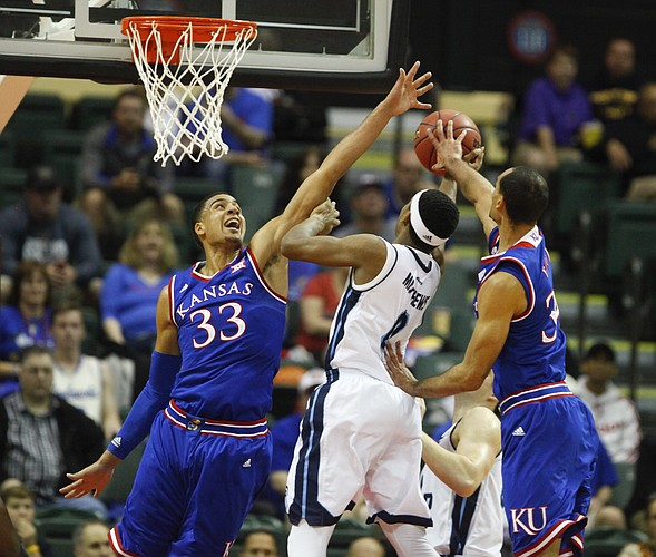 Kansas forward Landen Lucas (33) and forward Perry Ellis (34) smother a shot by Rhode Island guard E.C. Matthews (0) during the first half on Thursday, Nov. 27, 2014 at the HP Field House in Kissimmee, Florida.