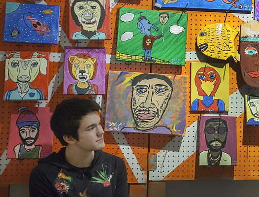 Lawrence High School freshman Max McGraw sits beneath some of his art work on sale at the annual Bizarre Bazaar at the Lawrence Arts Center, Friday, Nov. 28, 2014. The event continues Saturday from 9am to 5pm.