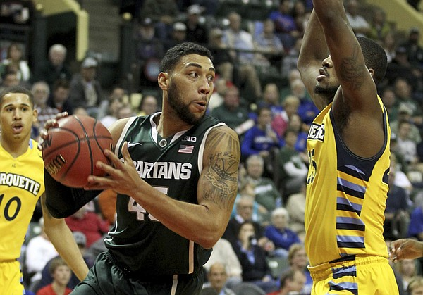 Michigan State guard Denzel Valentine (45) drives past Marquette Golden forward Steve Taylor Jr. (25) during the first half of an NCAA college basketball game in Kissimmee, Florida. MSU on Sunday will face Kansas in the championship game of the Orlando Classic.