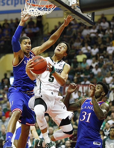 Kansas forward Landen Lucas, left, and forward Jamari Traylor (31) defend against a drive by Michigan State guard Bryn Forbes (5) during the second half on Sunday, Nov. 30, 2014 at the HP Field House in Kissimmee, Florida.