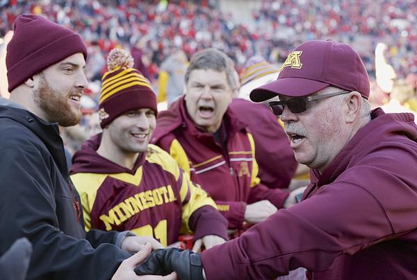 Minnesota head coach Jerry Kill, right, celebrates with fans a 28-24 win over Nebraska in an NCAA college football game in Lincoln, Neb., Saturday, Nov. 22, 2014. (AP Photo/Nati Harnik)