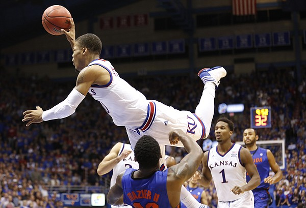 Kansas guard Frank Mason III (0) looks to dump a pass as he bowls over Florida guard Michael Frazier II (20) during the second half on Friday, Dec. 5, 2014 at Allen Fieldhouse.