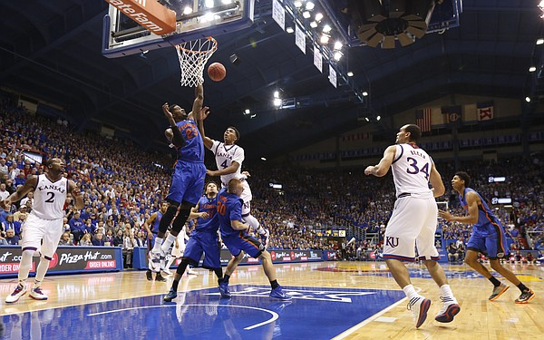 Kansas guard Devonte Graham (4) puts up a floater as he is fouled by Florida forward Jacob Kurtz (30) during the second half on Friday, Dec. 5, 2014 at Allen Fieldhouse.