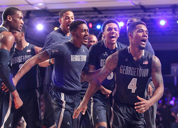 Georgetown's D'Vauntes Smith-Rivera (4), front, who scored the game-point, is surrounded by teammates as they celebrate their victory over Florida in the Battle 4 Atlantis basketball tournament in Paradise Island, Bahamas, Wednesday Nov. 26, 2014. (AP Photo/Tim Aylen)