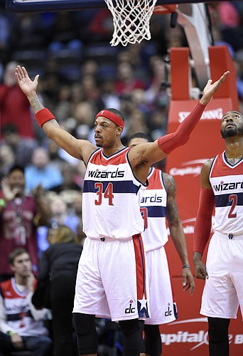 Washington Wizards forward Paul Pierce (34) raises his arms as he acknowledges the crowd after it was announced that he is now 16th all-time in points scored during the first half of an NBA basketball game against the Boston Celtics, Monday, Dec. 8, 2014, in Washington. The Wizards won 133-132 in double overtime. Also seen is Washington Wizards guard John Wall (2). (AP Photo/Nick Wass)