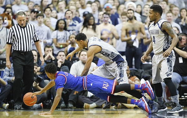 Kansas guard Devonte Graham (4) lays out while competing for a loose ball with Georgetown forward Isaac Copeland (11) during the first half on Wednesday, Dec. 10, 2014 at Verizon Center in Washington D.C. At right is Georgetown guard D'Vauntes Smith-Rivera (4).