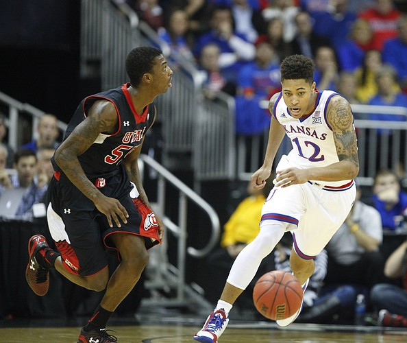 Kansas guard Kelly Oubre Jr. (12) eyes the ball as he defends Utah guard Delon Wright (55) during the first half on Saturday, Dec. 13, 2014 at Sprint Center