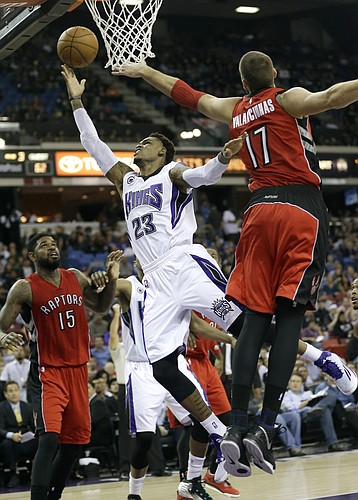 Sacramento Kings guard Ben McLemore, center, drives to the basket between Toronto Raptors Amir Johnson, left, and Jonas Valanciunas, of Lithuania, during the third quarter of an NBA basketball game in Sacramento, Calif., Tuesday, Dec. 2, 2014. The Raptors won 117-109. (AP Photo/Rich Pedroncelli)