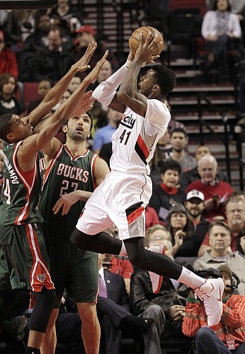 Portland Trail Blazers forward Thomas Robinson, right, shoots against Milwaukee Bucks forward Giannis Antetokounmpo, from Greece, left, and center Zaza Pachulia, from Ukraine, during the first half of an NBA basketball game in Portland, Ore., Wednesday, Dec. 17, 2014.(AP Photo/Don Ryan)