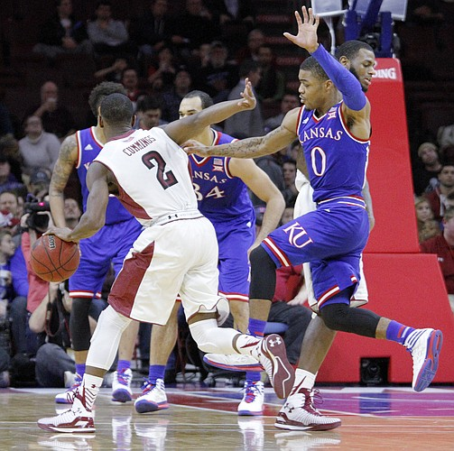Kansas guard Frank Mason III (0) tries to slide by a screen chasing Temple guard Will Cummings (2) Monday at the Wells Fargo Center in Philadelphia, PA.