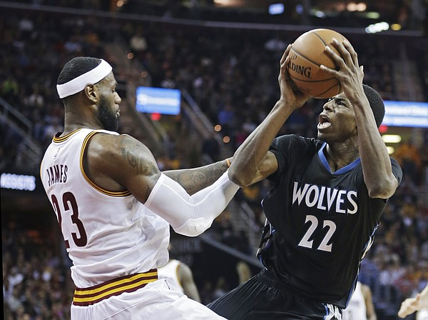 Minnesota Timberwolves' Andrew Wiggins (22) is fouled by Cleveland Cavaliers' LeBron James during the third quarter of an NBA basketball game Tuesday, Dec. 23, 2014, in Cleveland. Wiggins led the Timberwolves with 27 points, but the Cavaliers won 125-104. (AP Photo/Mark Duncan)