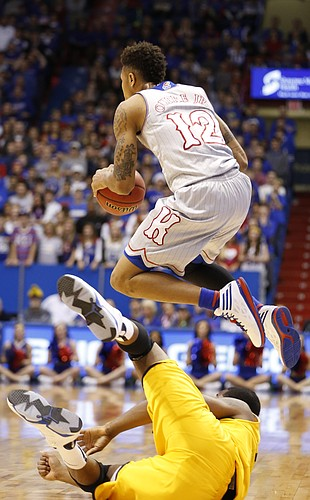 Kansas guard Kelly Oubre Jr. (12) jumps over Kent State center Khaliq Spicer (21) to save a loose ball during the first half on Tuesday, Dec. 30, 2014 at Allen Fieldhouse.