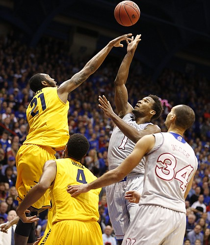 Kent State center Khaliq Spicer (21) gets a piece of a shot by Kansas guard Wayne Selden Jr. (1) during the first half on Tuesday, Dec. 30, 2014 at Allen Fieldhouse.