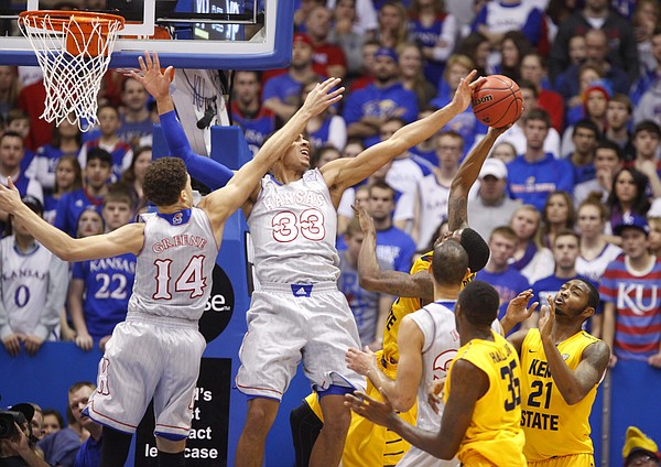 Kansas forward Landen Lucas (33) draws some contact from teammate Brannen Greene (14) as he blocks a shot by Kent State guard Kris Brewer (1) during the first half on Tuesday, Dec. 30, 2014 at Allen Fieldhouse.