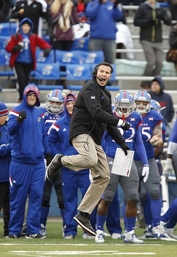 Kansas interim head coach Clint Bowen gets airborne as he celebrates a fourth-down stop against TCU during the first quarter on Saturday, Nov. 15, 2014 at Memorial Stadium.