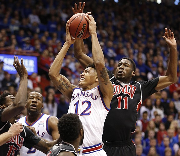 Kansas guard Kelly Oubre Jr. (12) has his shot stuffed by UNLV forward Goodluck Okonoboh (11) during the first half against UNLV on Sunday, Jan. 4, 2015 at Allen Fieldhouse.