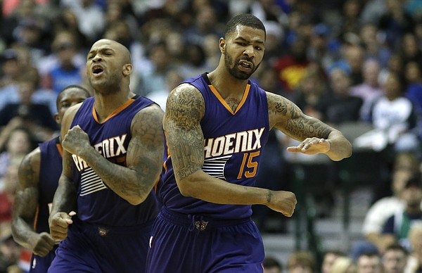 Phoenix Suns forwards Marcus Morris (15) and P.J. Tucker celebrate during the second half of an NBA basketball game against the Dallas Mavericks Friday, Dec. 5, 2014, in Dallas. (AP Photo/LM Otero)