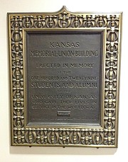 "This small plaque, inscribed as a gift of the class of 1924, is displayed on the main level of the Kansas Union. It reads, ""Kansas Memorial Union Building, erected in memory of the one hundred and twenty nine students and alumni of the University of Kansas who gave their lives in service in the world war."" A few other World War I related wall displays appear on the sixth floor of the Union."