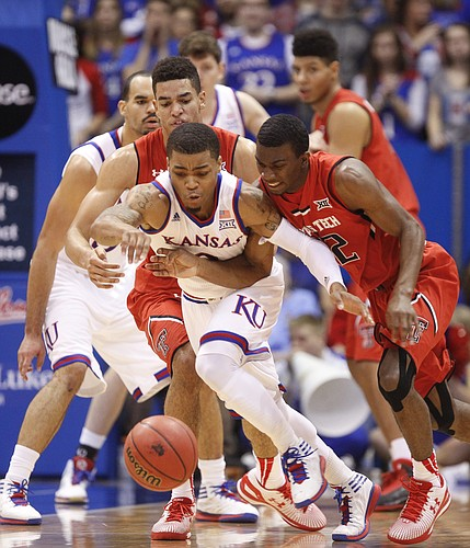 Kansas guard Frank Mason III (0) hustles for a loose ball after knocking it away from Texas Tech guard Keenan Evans (12) during the first half on Saturday, Jan.10, 2015 at Allen Fieldhouse.
