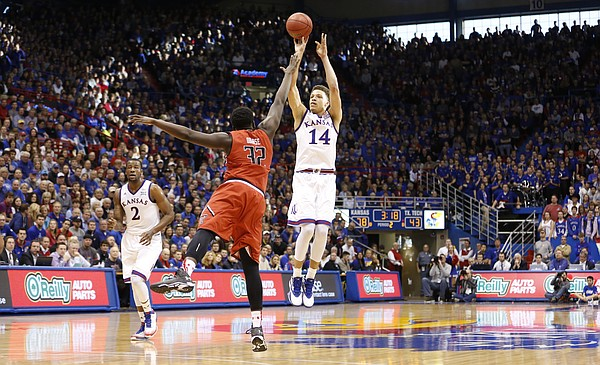 Kansas guard Brannen Greene (14) puts up a three over Texas Tech forward Norense Odiase (32) during the second half on Saturday, Jan.10, 2015 at Allen Fieldhouse. At left is Kansas forward Cliff Alexander (2)