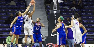 Kansas' Natalie Knight (42) and Chayla Cheadle (22) defend a shot attempt by Kansas State senior guard Ashia Woods (23)  during the second half of their game Sunday afternoon at Bramlage Coliseum in Manhattan. Despite a quick start by the Jayhawks that saw them surge to a 14 point lead, Kansas fell to the Wildcats, 58-52, and dropped to 0-3 in Big 12 play.