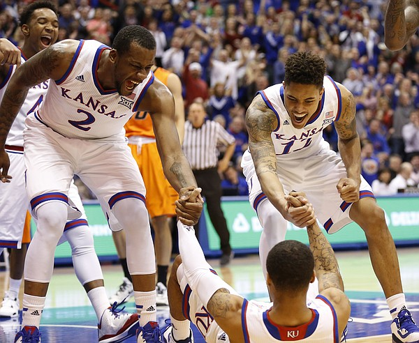 Teammates Kansas forward Cliff Alexander (2) and guard Kelly Oubre Jr. (12) come in to celebrate with Frank Mason III after Mason drew a foul on a bucket during the first half, Tuesday, Jan. 13, 2015 at Allen Fieldhouse.