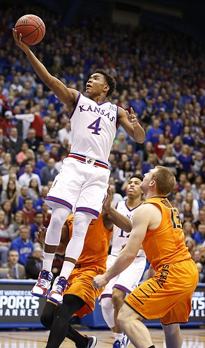 Kansas guard Devonte Graham (4) floats in for a bucket over Oklahoma State guard Phil Forte III (13) during the first half, Tuesday, Jan. 13, 2015 at Allen Fieldhouse.