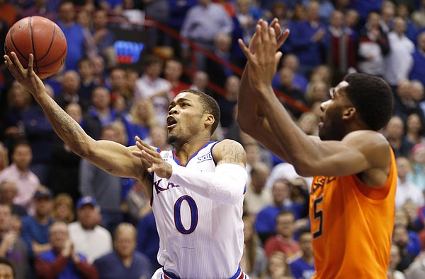 Kansas guard Frank Mason III (0) heads to the hoop against Oklahoma State forward Tavarius Shine (5) during the first half, Tuesday, Jan. 13, 2015 at Allen Fieldhouse.