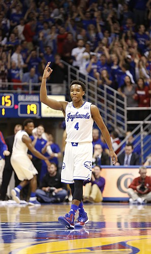 Kansas guard Devonte Graham (4) holds up three fingers to celebrate his shot beyond the arc that shot high off the rim and down through the net during the first half on Monday, Jan. 19, 2015 at Allen Fieldhouse.