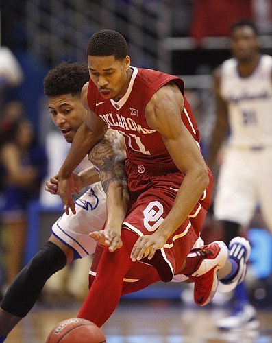 Kansas guard Kelly Oubre Jr. reaches through for a steal against Oklahoma guard Isaiah Cousins (11) during the first half on Monday, Jan. 19, 2015 at Allen Fieldhouse.
