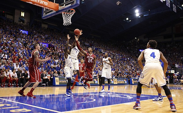 Oklahoma guard Buddy Hield (24) puts up a shot as he is defended by the Jayhawks during the second half on Monday, Jan. 19, 2015 at Allen Fieldhouse.