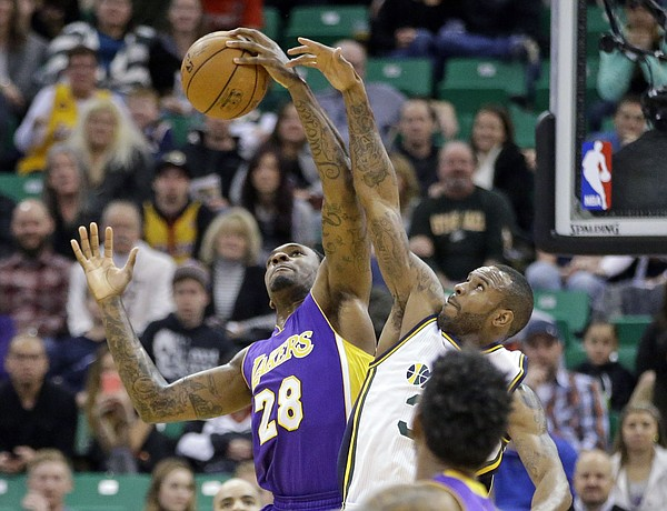 Los Angeles Lakers forward Tarik Black (28) pulls down a rebound from Utah Jazz forward Trevor Booker, right, in the second quarter during an NBA basketball game Friday, Jan. 16, 2015, in Salt Lake City. (AP Photo/Rick Bowmer)
