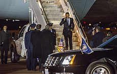 President Barack Obama gives a salute as he walks down the steps from Air Force One while Governor Sam Brownback waits Thursday evening at Forbes Field in Topeka.