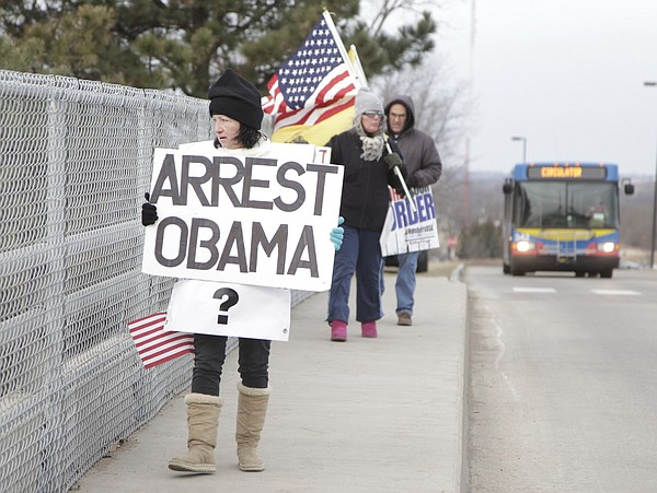 Protestors with Overpasses for America, display signs on the bridge over Iowa St., that links Daisy Hill to West Campus at KU. The group was protesting President Obama before he delivered a speech Thursday, Jan. 22, 2015 on the KU campus.
