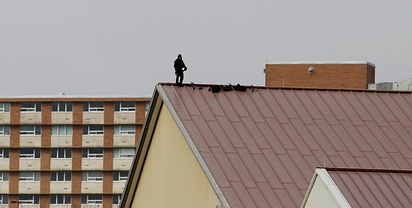 A security officer stands on the roof of Anschutz Sports Pavilion during President Barack Obama's speech Thursday, Jan. 22, 2015.