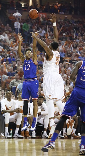 Kansas guard Kelly Oubre Jr. (12) puts up a three over Texas center Cameron Ridley (55) during the first half, Saturday, Jan. 24, 2015 at Frank Erwin Center in Austin, Texas.