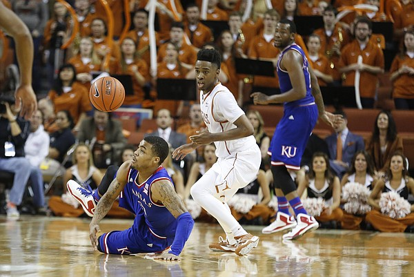 Kansas guard Frank Mason III (0) loses the ball after slipping on the court while defended by Texas guard Isaiah Taylor (1) during the second half, Saturday, Jan. 24, 2015 at Frank Erwin Center in Austin, Texas.