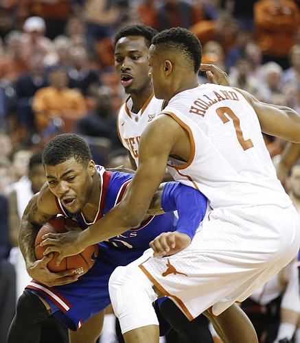 Kansas guard Frank Mason III (0) shrugs off Texas defenders Demarcus Holland (2) and guard Kendal Yancy during the second half, Saturday, Jan. 24, 2015 at Frank Erwin Center in Austin, Texas.