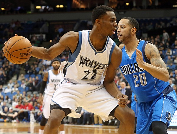 Minnesota Timberwolves' Andrew Wiggins (22) tries to move around Dallas Mavericks' Devin Harris (20) in the first quarter of an NBA basketball game, Wednesday, Jan. 21, 2015, in Minneapolis. (AP Photo/Jim Mone)