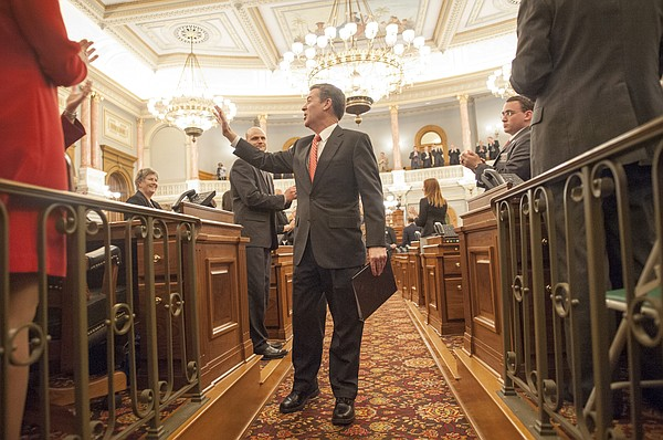Kansas Gov. Sam Brownback waves after delivering his State of the State address to a combined session at the Kansas State Capitol on Thursday, Jan. 15, 2015, in Topeka.