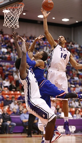 Kansas guard Frank Mason III (0) has a shot blocker by TCU Horned Frogs center Karviar Shepherd (14) during the first half at Wilkerson-Greines Activity Center on Wednesday, Jan. 28, 2015 in Fort Worth, Texas.