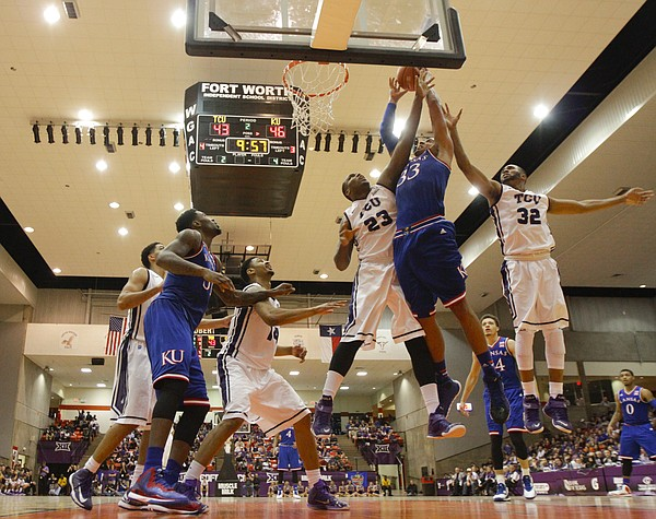 Kansas forward Landen Lucas (33) is fouled on his way to the bucket while defended by TCU Horned Frogs forward Devonta Abron (23) and guard Trey Zeigler (32) during the second half at Wilkerson-Greines Activity Center on Wednesday, Jan. 28, 2015 in Fort Worth, Texas.