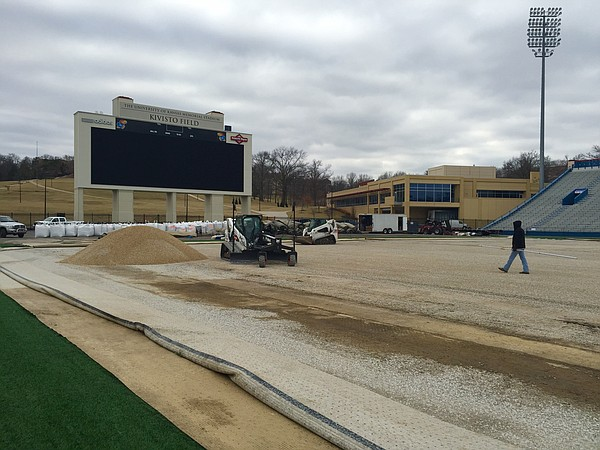 Construction crews in charge of installing new turf at Memorial Stadium work to level out the playing surface on Thursday, Jan. 29, 2015