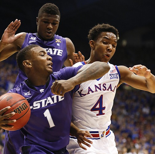 Kansas guard Devonte Graham (4) pressures Kansas State guard Jevon Thomas (1) during the first half on Saturday, Jan. 31, 2015 at Allen Fieldhouse. In back is Kansas State guard Malek Harris.
