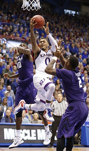 Kansas guard Frank Mason III (0) squeezes in for a bucket against Kansas State guard Malek Harris (10) and guard Marcus Foster (2) during the second half on Saturday, Jan. 31, 2015 at Allen Fieldhouse.