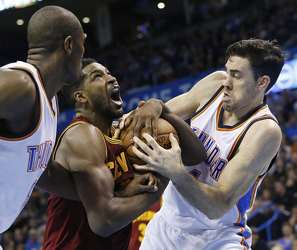 Cleveland Cavaliers forward Tristan Thompson, center, fights for the ball with Oklahoma City Thunder forward Serge Ibaka, left, and forward Nick Collison, right, in the second quarter of an NBA basketball game in Oklahoma City, Thursday, Dec. 11, 2014. Oklahoma City won 103-94. (AP Photo/Sue Ogrocki)