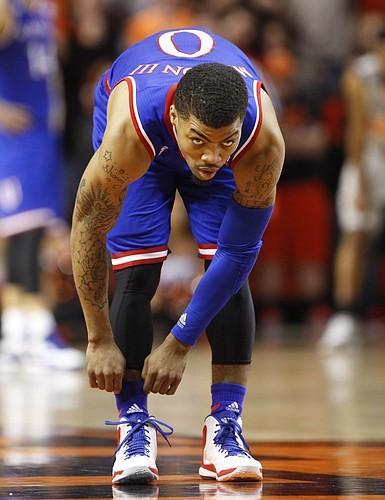 Kansas guard Frank Mason III (0) eyes his man while adjusting his socks at half court during the first half on Saturday, Feb. 7, 2015 at Gallagher-Iba Arena.