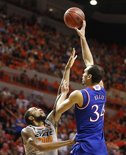 Kansas forward Perry Ellis (34) turns for a shot over Oklahoma State forward Jeffrey Carroll during the second half on Saturday, Feb. 7, 2015 at Gallagher-Iba Arena.