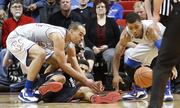 Kansas forward Perry Ellis, left, and guard Frank Mason III, go for a loose ball during the Jayhawks 73-51 win over Texas Tech Tuesday, Feb. 10, 2015 at United Supermarkets Arena.