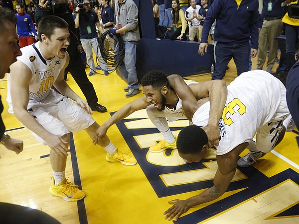 West Virginia guards Chase Connor, left, and Gary Browne, center, surround Juwan Staten (3) at the end of the Mountaineers 62-61 win over the Jayhawks Monday, February 16, 2105  in Morgantown, W.V. Staten scored the final basket for the win.